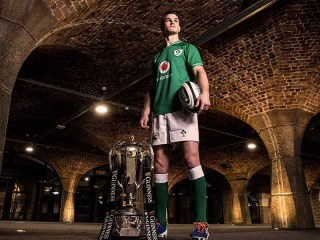 Jonathan Sexton holding a rugby ball beside the Guinness Six Nations cup